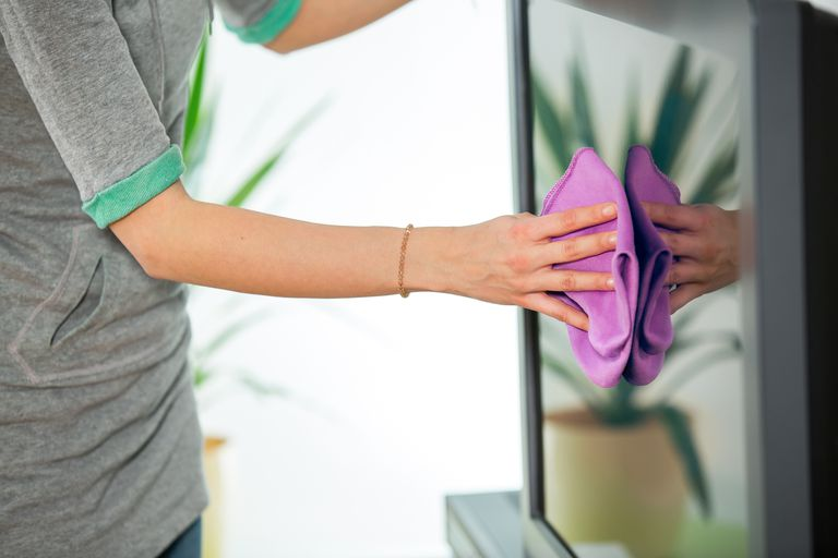 Picture of a woman cleaning a TV screen with a microfiber cloth