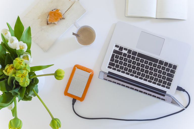 Home office: High angle view or directly above view of laptop with external hard disk drive and flower vase on white table