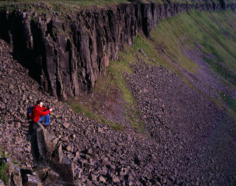 Hiker in britain sitting above scree field