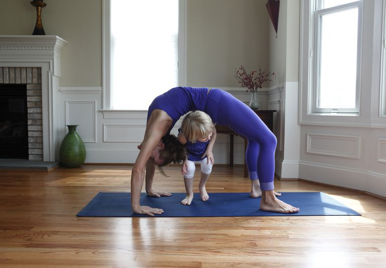 Mother and child practicing yoga and playing