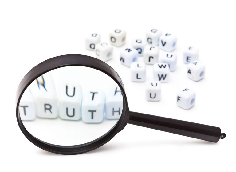 the word truth spelled out beneath a magnifying glass