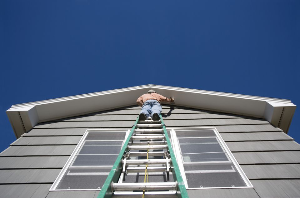Man painting house on ladder