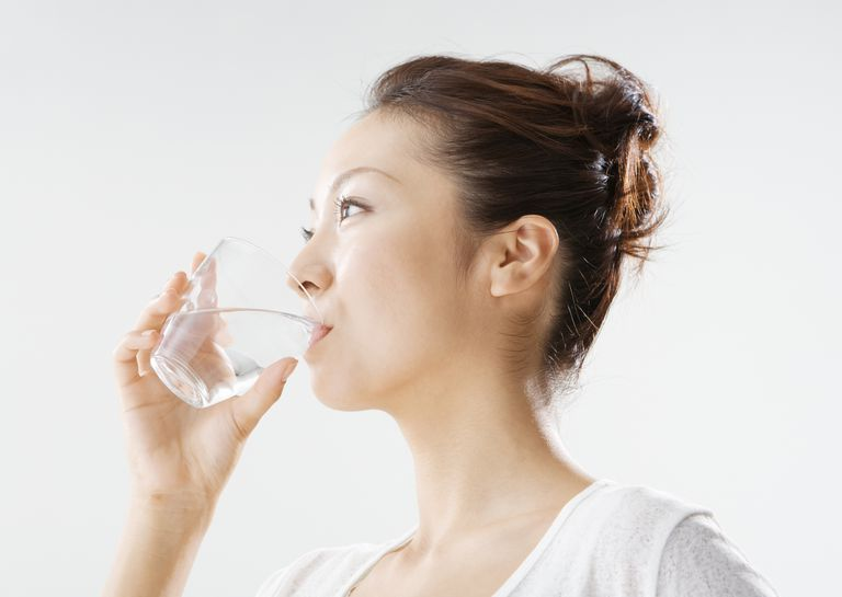 woman using mouth wash from glass