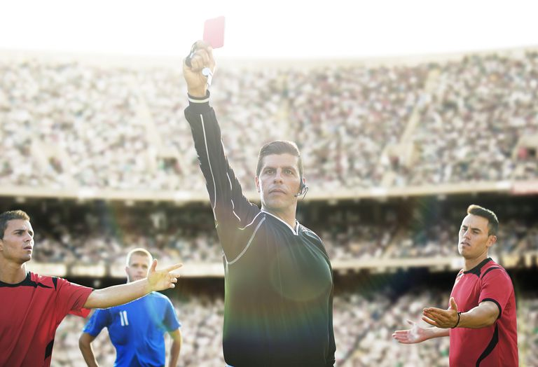 Referee flashing red card in soccer game