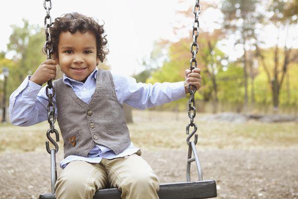 Mixed race boy sitting on swing in park