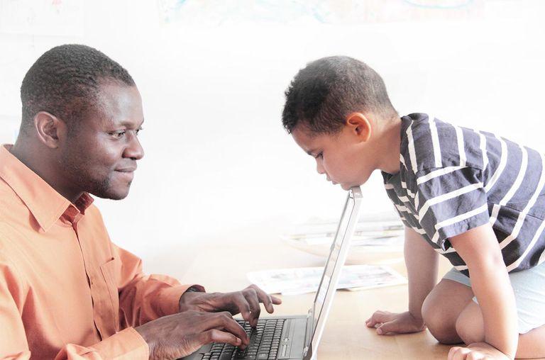 Boy watching father use laptop