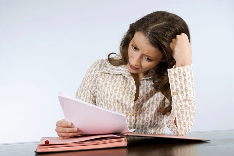 Young woman reading document scratching head