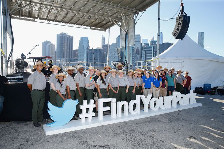 Group of parks rangers stand behind a sign advertising the National Parks Service's Find Your Park campaign.