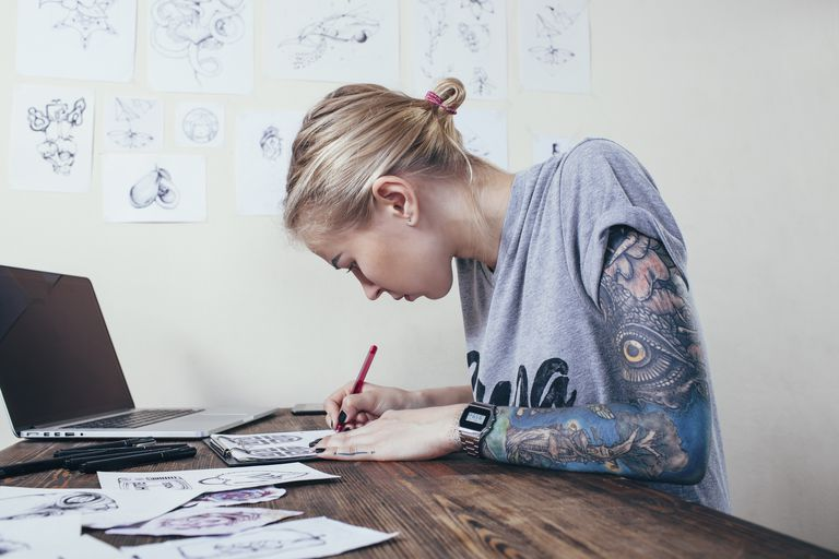 An artist in their studio works on a tattoo design.