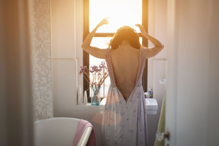 Woman standing at a window, light coming in, in pain from adhesions