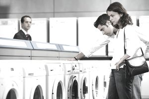 Couple looking at washing machine in aisle of department store