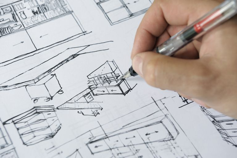 Close-up of hand with pen sketching a custom kitchen. Architects Design for  YOU.