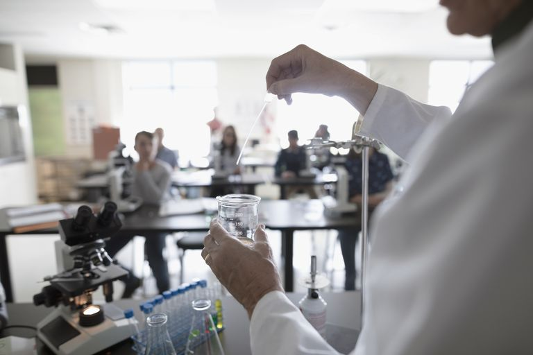 Students watching science teacher conducting scientific experiment in laboratory