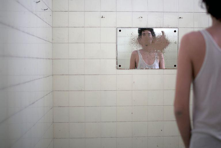 Man looking in dirty mirror