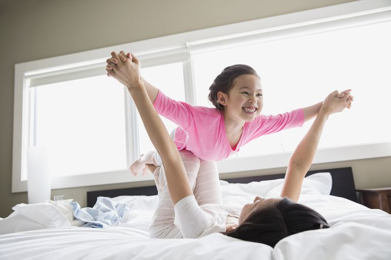 Girl playing airplane with mom