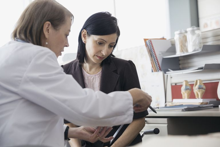 Doctor reviewing medical record with patient in office