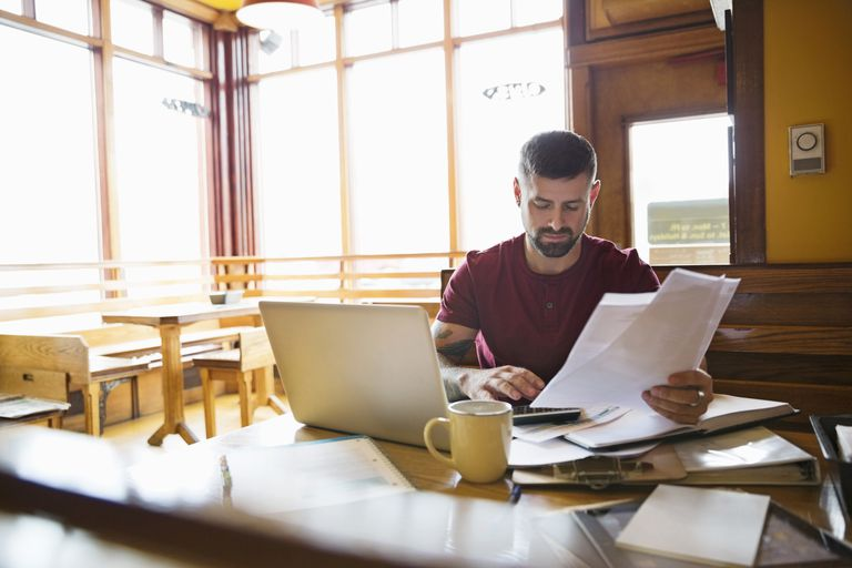 man looking at paperwork and laptop in restaurant