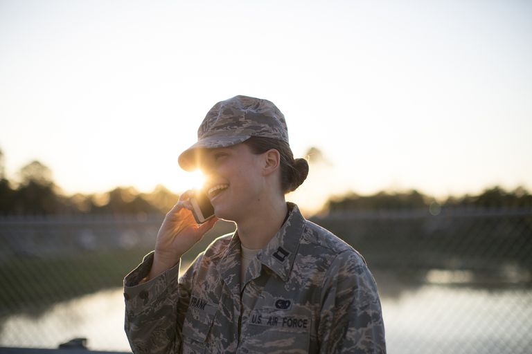 Female soldier talking on smartphone from wire fence at air force military base