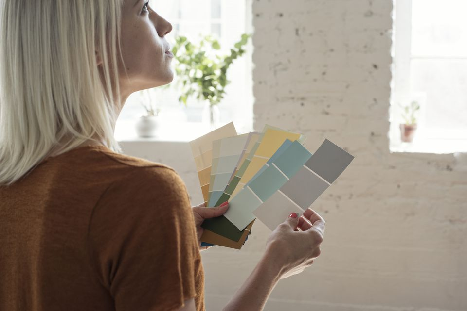 Young woman in a loft thinking about color samples