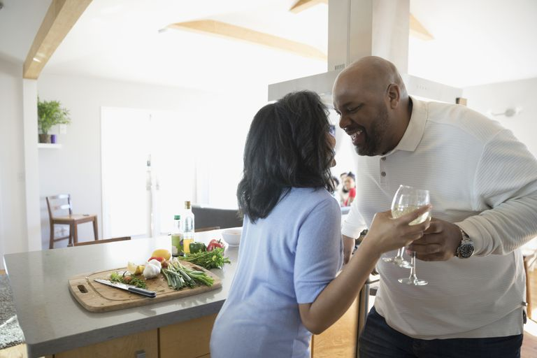 Playful African American couple dancing and drinking white wine in kitchen