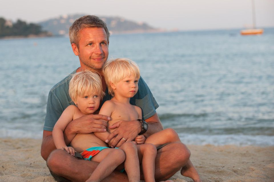 Father with identical young blonde twin boys