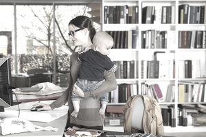 Mother at desk holding baby