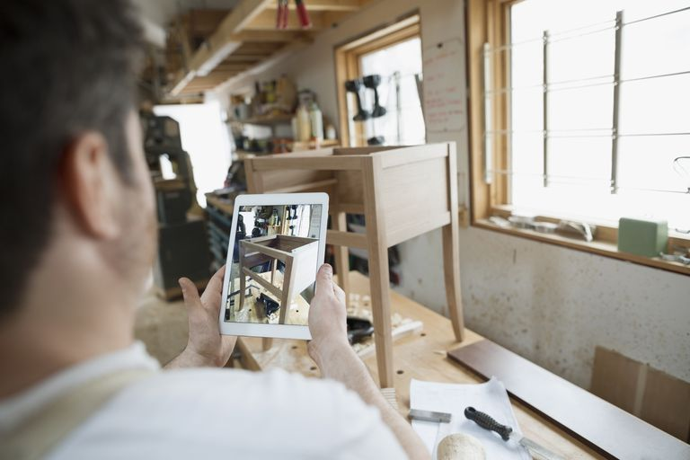 man taking photo of furniture he built with tablet