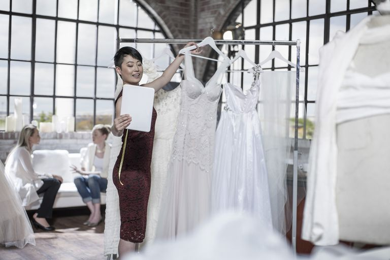 Wedding dress designer taking a photo with tablet