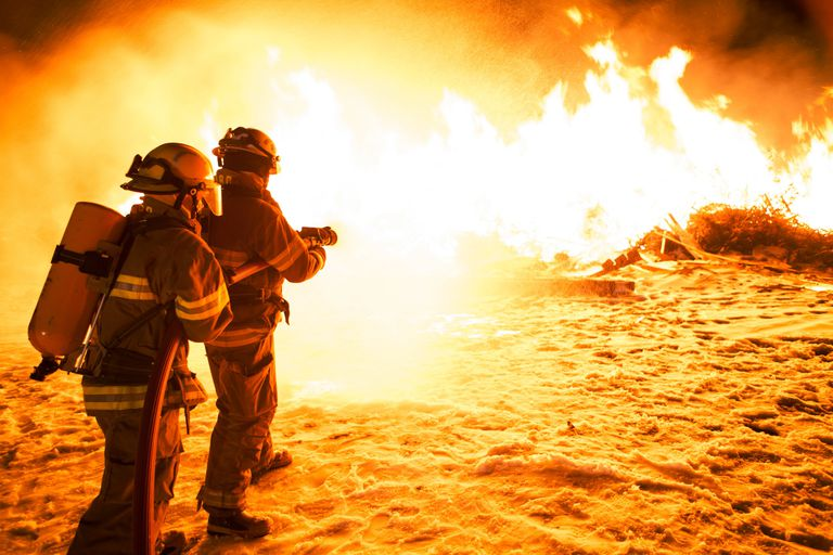 two firefighters spraying a fire