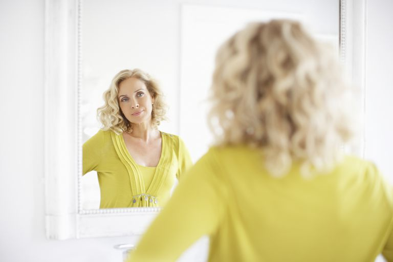 blond woman looking at herself contentedly in mirror
