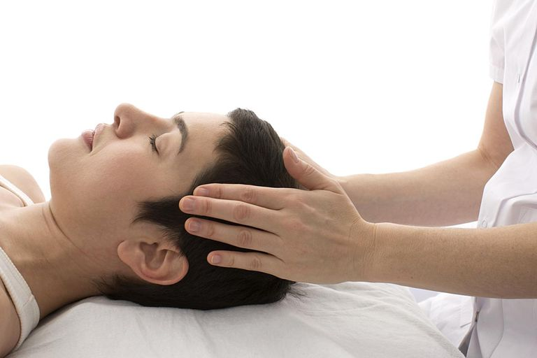 Patient getting massaging by acupuncturist, side view