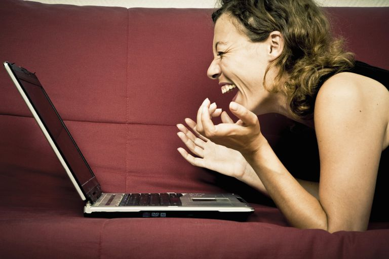 Woman laughing at her laptop