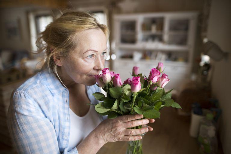 Older woman smelling flowers