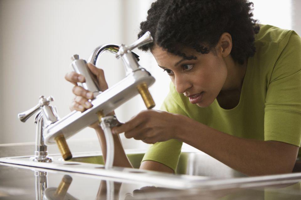Mixed race woman installing faucet