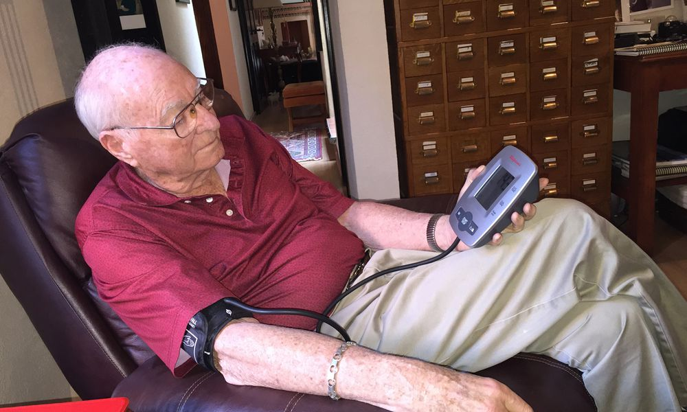 Older man sitting in a recliner taking his blood pressure