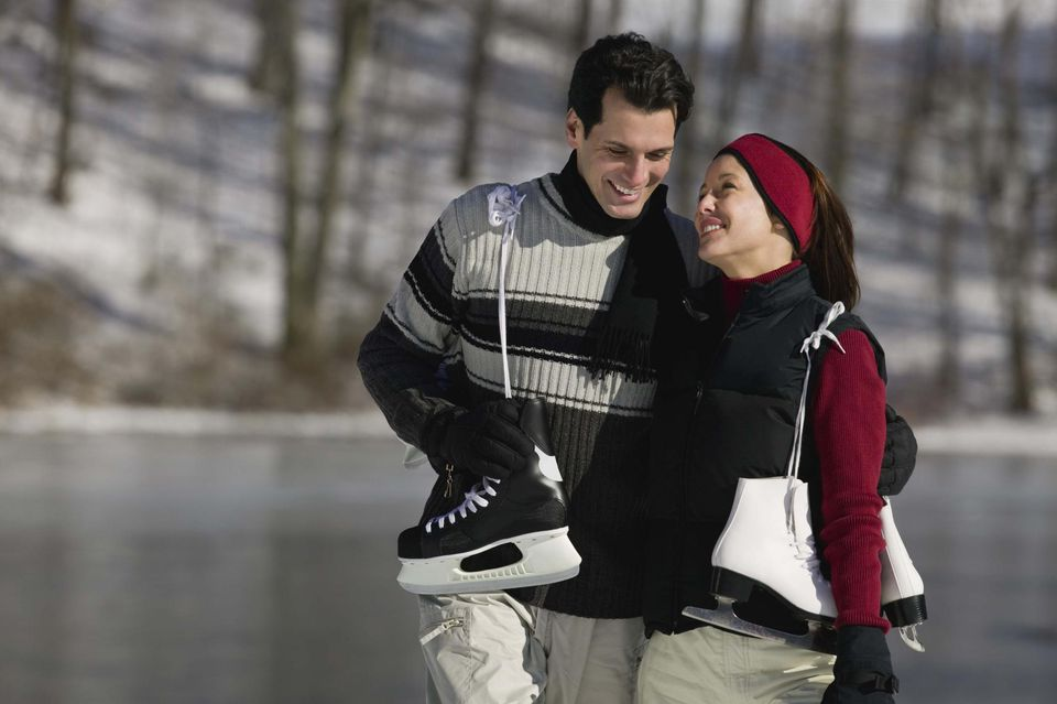 Smiling couple with ice skates