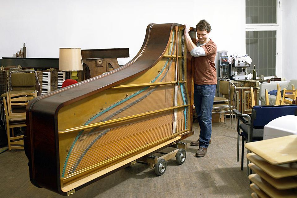 man pushing piano on wheels in workshop