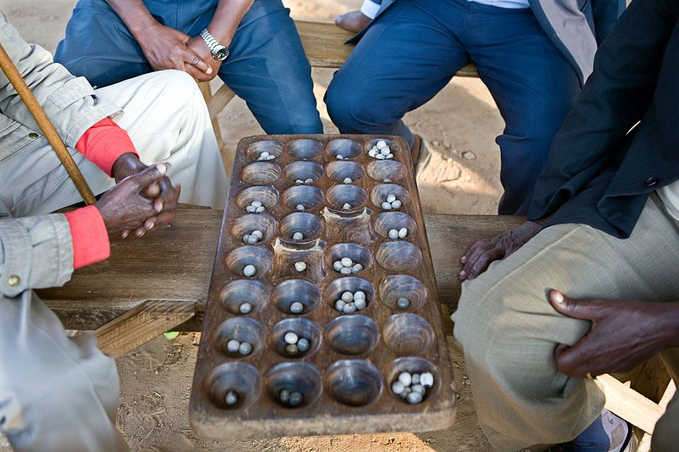 Elderly Muslim men sitting around the market in Iringa, Tanzania, playing a game called Bao. Bao has many names all over the world but is probably best known as Mancala.