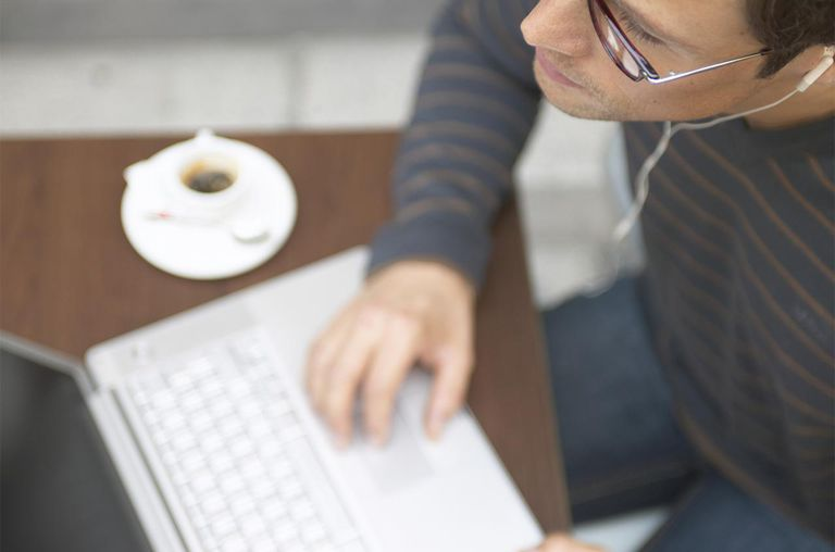 Man sitting at cafe table using laptop computer, close-up