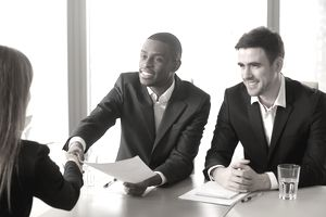 Black and white hr recruiters welcoming applicant on job interview