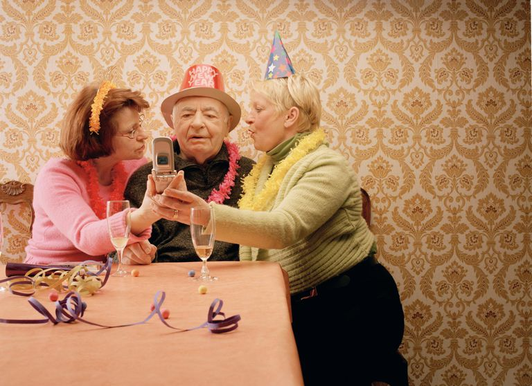 Two mature women showing senior man mobile phone, wearing party hats