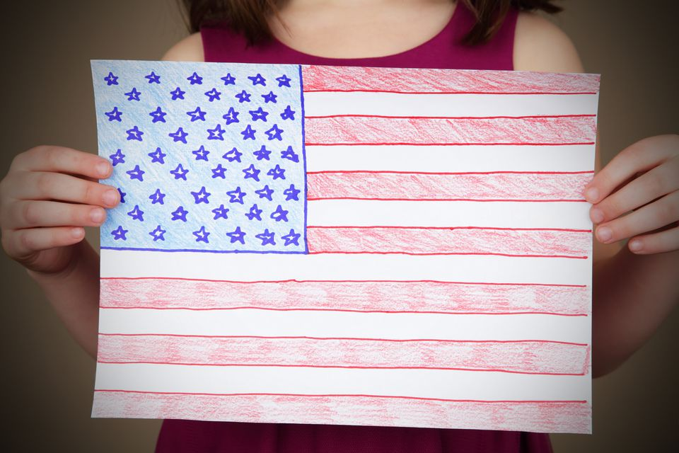 A young girl proudly shows off her drawing of the American Flag.