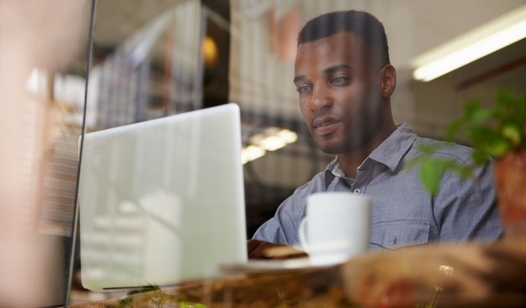 Cropped shot of a young african man using his laptop in a coffee shop