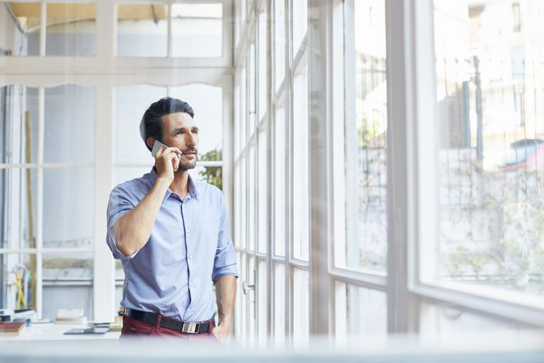 Businessman using mobile phone standing in office