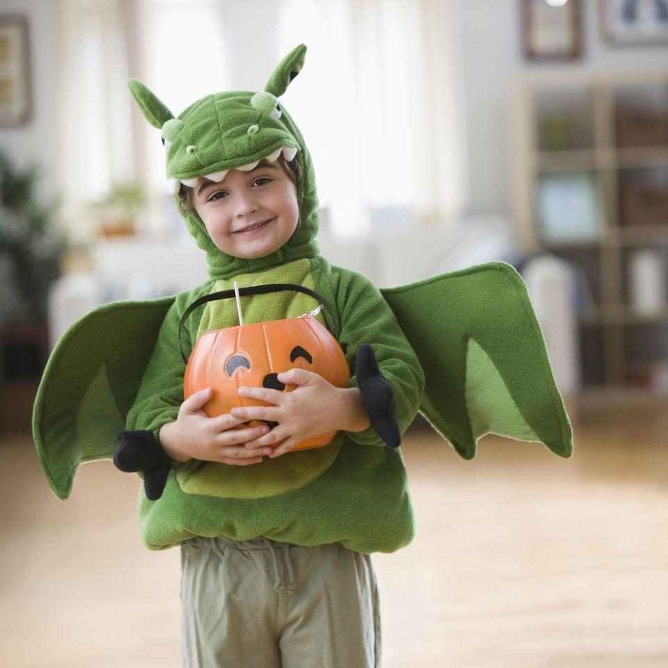 Mixed race boy in Halloween dragon costume