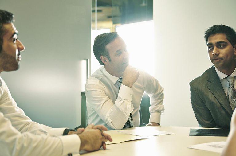 Business men sitting around meeting table