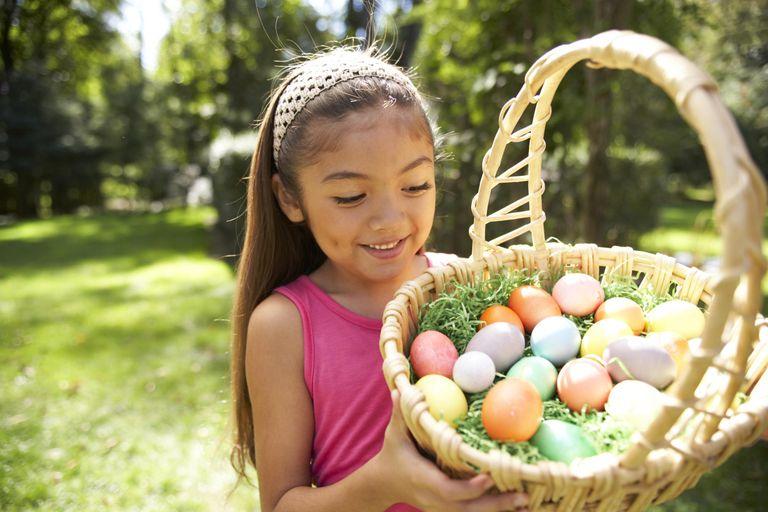 Girl (6-7) holding Easter basket in garden