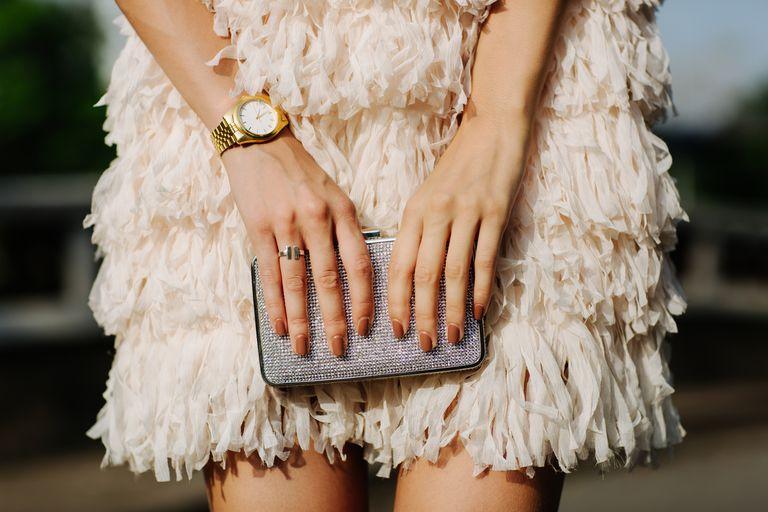 Woman in fancy dress holding clutch bag