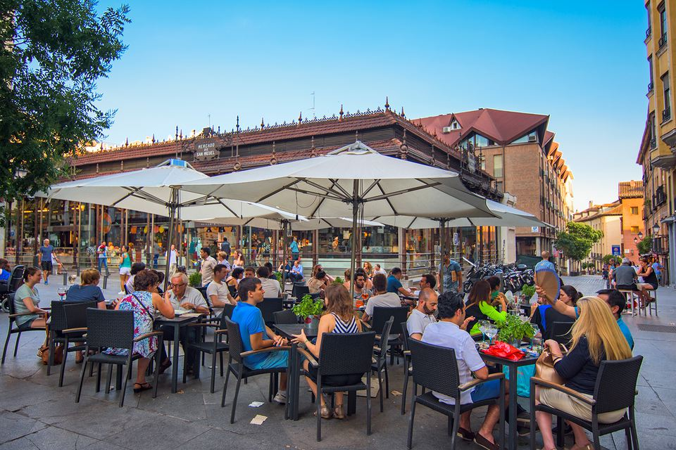 People sitting at an Outdoor bar with sunshades. Next to the Plaza Mayor of Madrid (Spain).