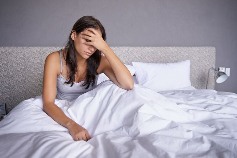 woman holding head in bed